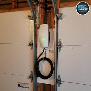 Tesla gen 3 wall connector installed between garage doors by MDC Electric